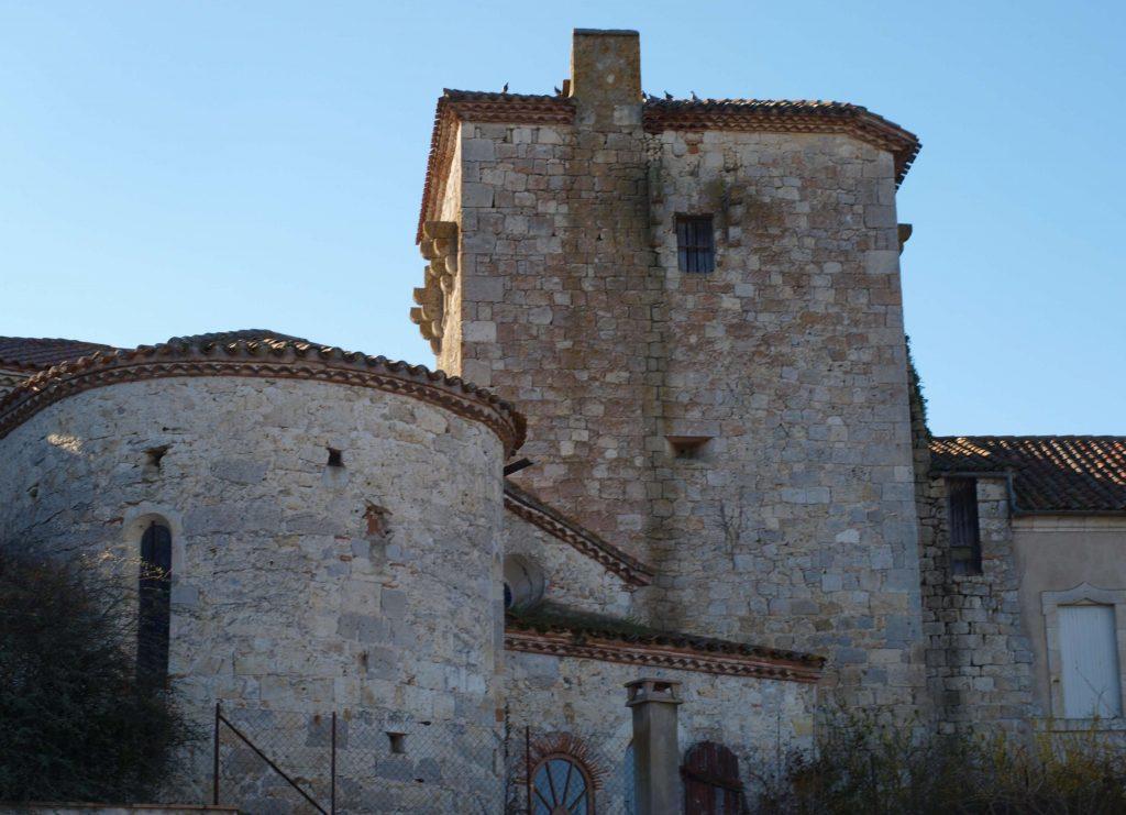 Tour du château avec sur la gauche l'église et sur la droite le presbytère